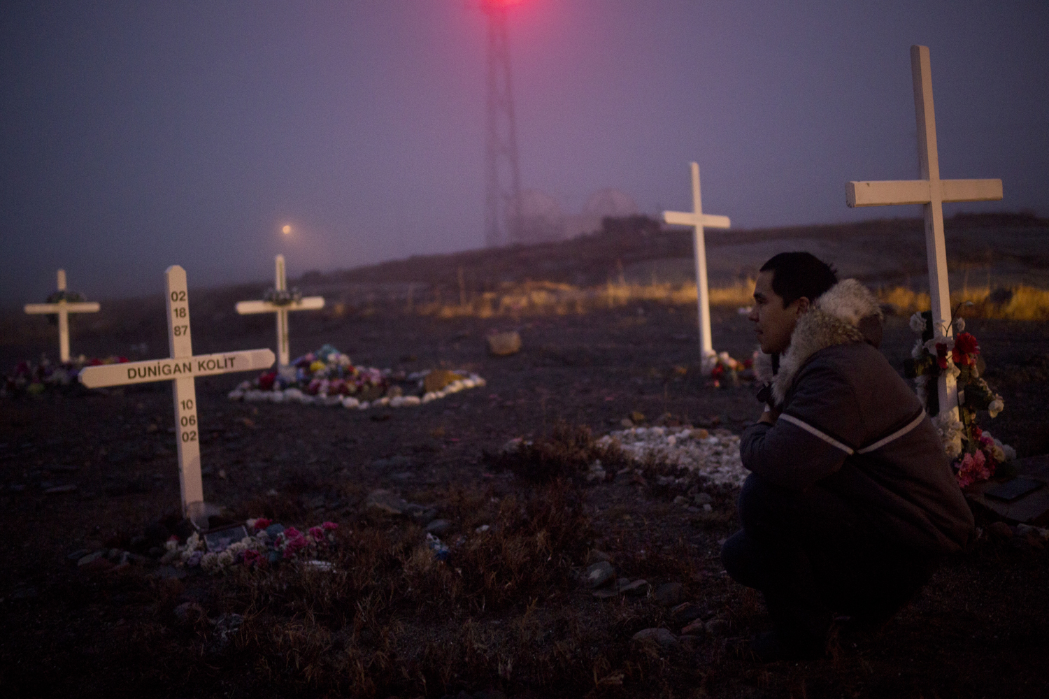 Rankin Inlet, Canada, Oct. 12, 2013. Brian Tagalik, 28, visits the grave of his friend Dunigan Kolit, who killed himself when he was 15-years old. As Brian walks throughout the cemetery, he points out the graves of almost a dozen of his friends who died of suicide.