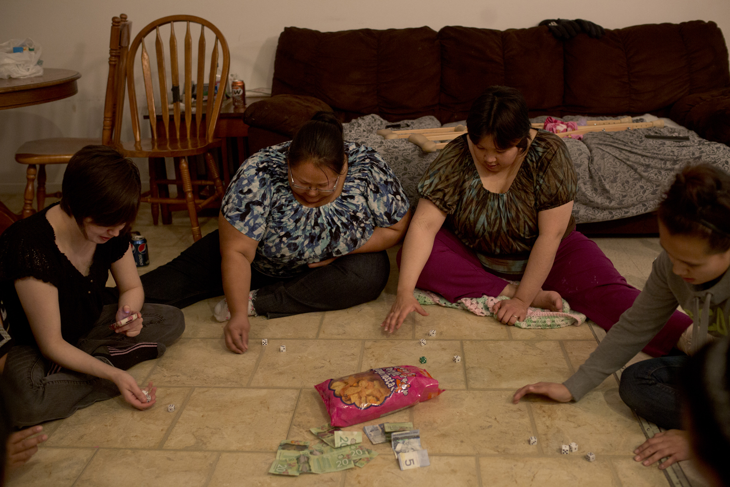 Arviat, Canada, Oct. 19, 2013. Kristy Cablutsiak, Sharon Aulatjut, and Katelyn Tiktaq gather to play 'Frankies', a dice game. Everyone puts money into a pool at the beginning of each game, and players must roll a consecutive combination of matching dice to win the pot. The game is played until the money runs out.
