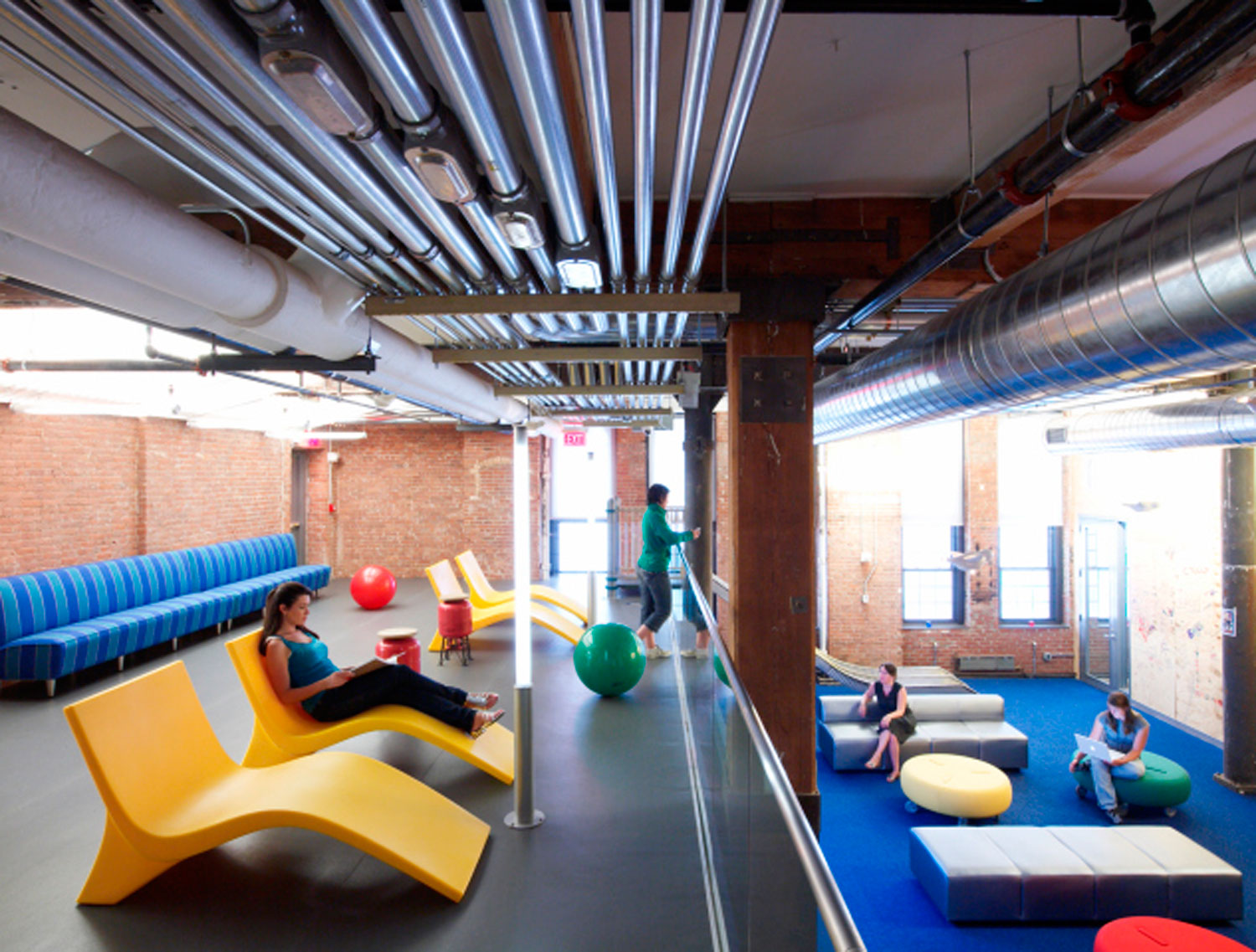 A lounge and workspace in Google's Chelsea Market office where employees can get together for a meeting or relax on a lounge chair.