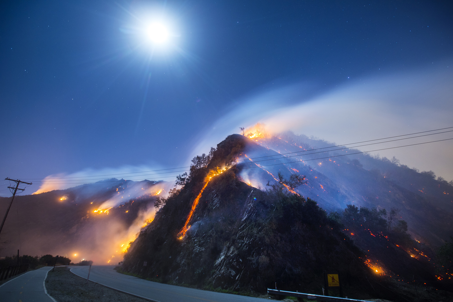 A full moon rises over the active flank of the Colbert Fire off San Gabriel Canyon Road in Azusa, Calif., Thousands of people were under mandatory evacuation orders overnight, Jan. 17,  2014.