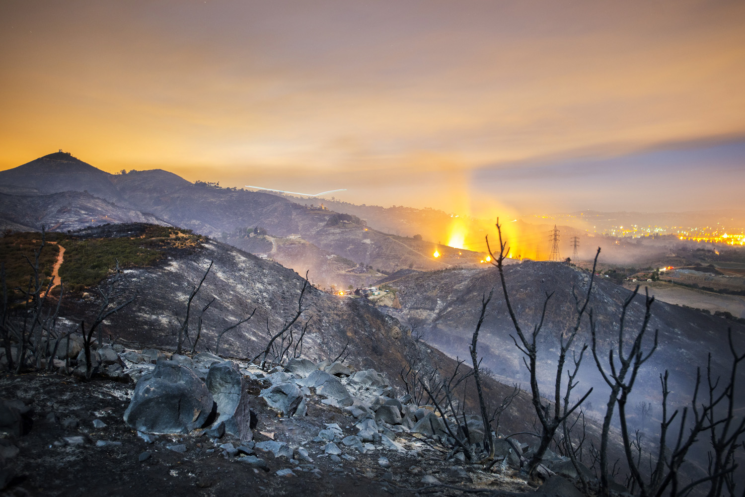 A long exposure shows smoldering remains of overnight fires on the hillsides of San Marcos, San Diego county, Calif., USA, early May 16, 2014.