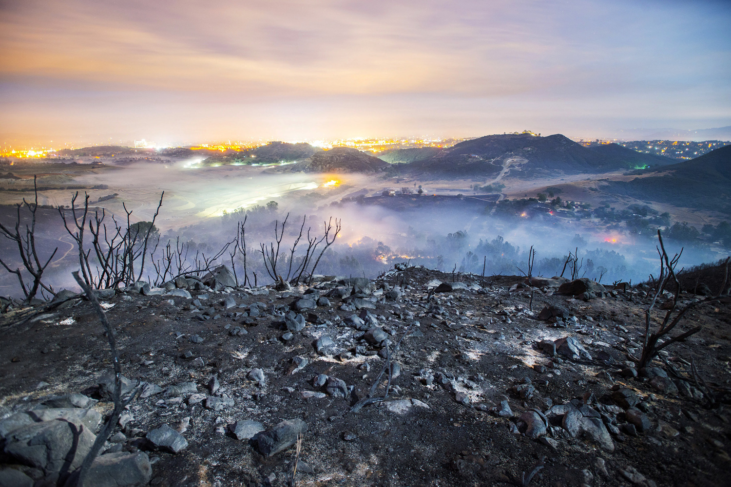 A long exposure shows smolderings remains of overnight fires on the hillsides of San Marcos, San Diego county, Calif., May 16, 2014.