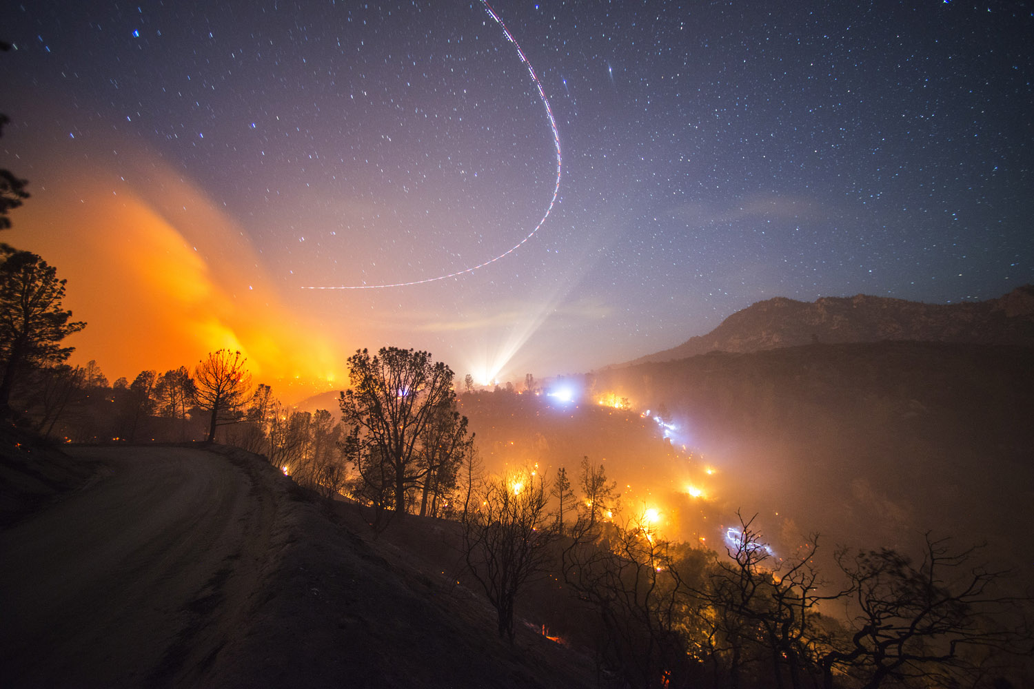 The Shirley Fire burns at night off of Old State Rd near Lake Isabella  while a helicopter circles overhead and crews work on a slopover, Calif., June 15, 2014.