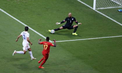 Goalkeeper Tim Howard of the USA saves a shot by Divock Origi of Belgium as Omar Gonzalez of the USA looks on during the national anthems prior the FIFA World Cup 2014 round of 16 match between Belgium and the USA at the Arena Fonte Nova in Salvador, Brazil on July 1, 2014.