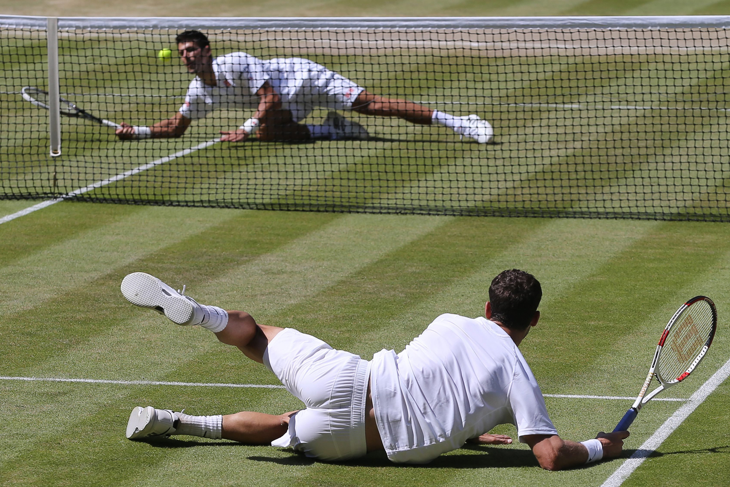 Jul. 4, 2014. Novak Djokovic of Serbia (top) and Grigor Dimitrov of Bulgaria both take a fall in their semi final match during the Wimbledon Championships at the All England Lawn Tennis Club, in London.