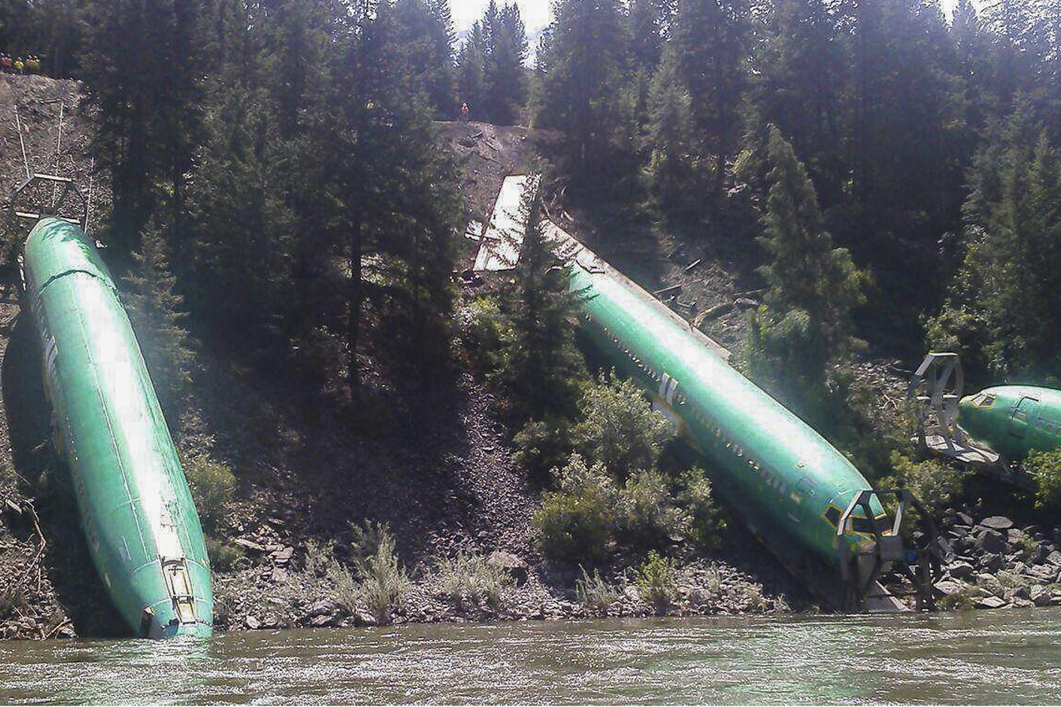 Jul. 6, 2014. The fuselages of three Boeing 737 aircraft around the Clark Fork River after the Montana Rail Link train they were being transported on derailed near Missoula, Montana.