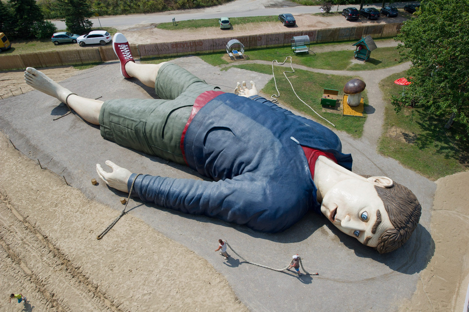 Workers carry a rope next to a figure of Gulliver at the amusement park 'Gulliver's World' in Pudalga on Usedom, Germany, July 8, 2014.
