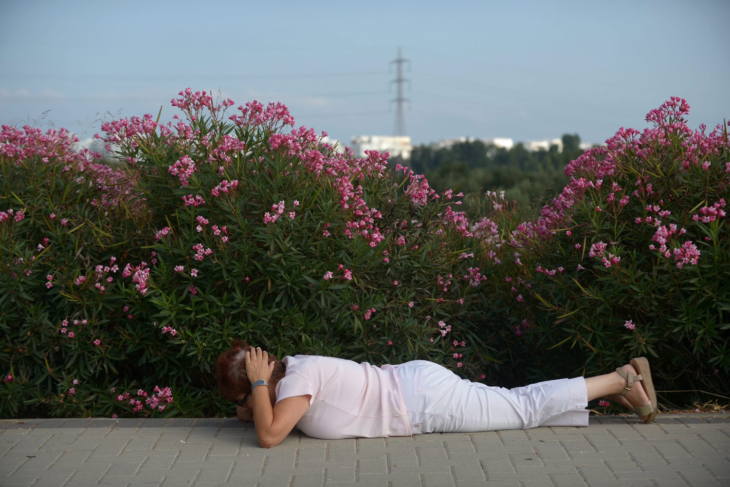 Jul. 9, 2014. An Israeli woman covers her head and lays on the ground while sirens sound in the southern city of Ashdod, Israel.
