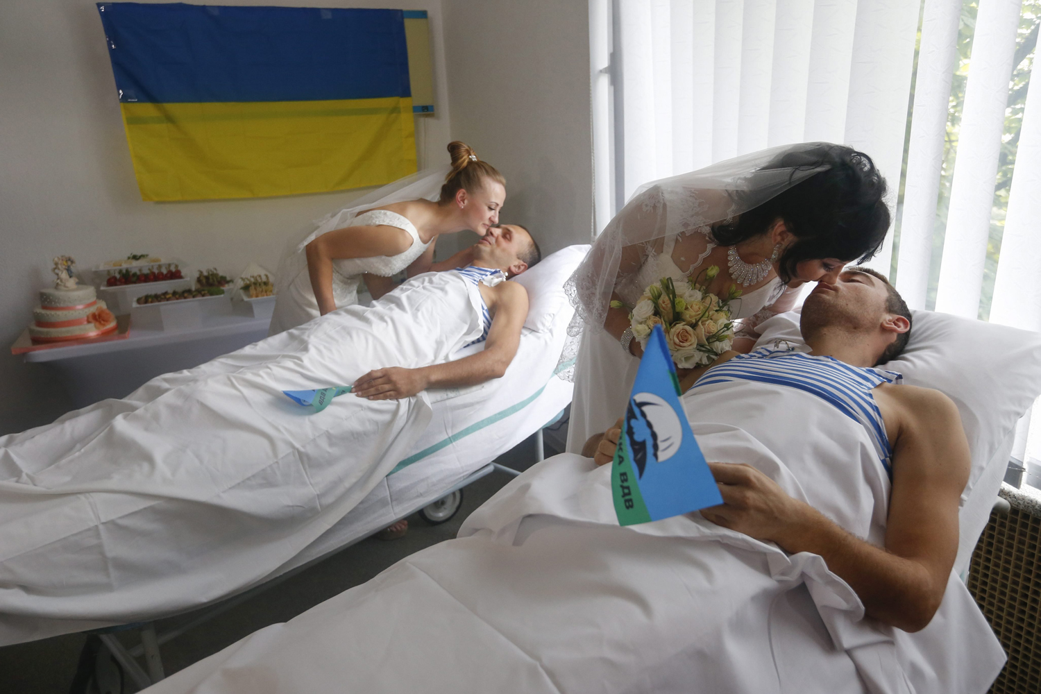 Jul. 9, 2014. Wounded members of the Ukrainian forces, paratroopers Ruslan Yarish (R) and Oleksandr Ponomaryov (L) kiss their brides during their wedding in the central military hospital in Kiev, Ukraine.