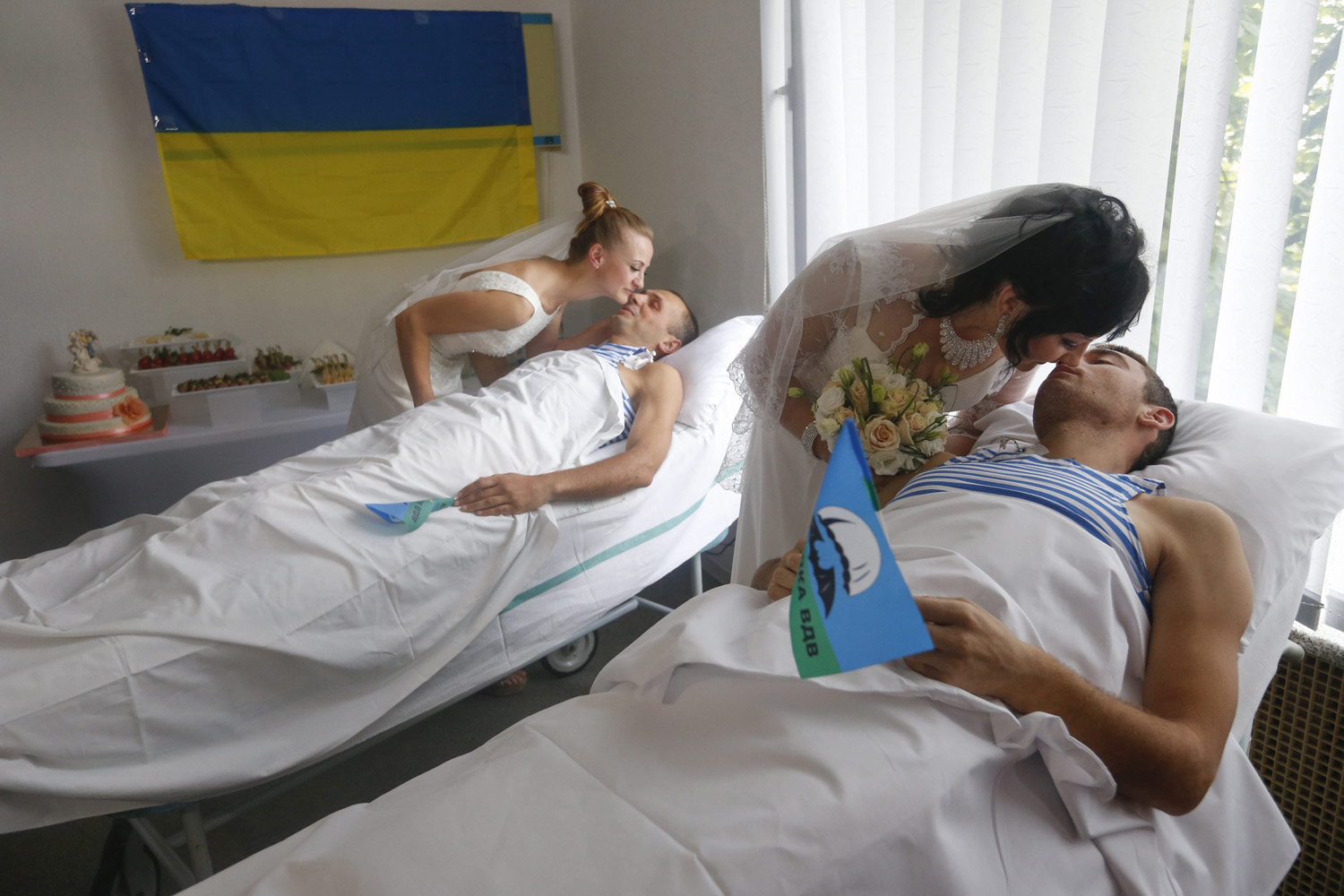 Wounded members of the Ukrainian forces, Ukrainian paratroopers Ruslan Yarish (R) and Oleksandr Ponomaryov (L) kiss their brides during their wedding in the central military hospital in Kiev, Ukraine on July 9, 2014.