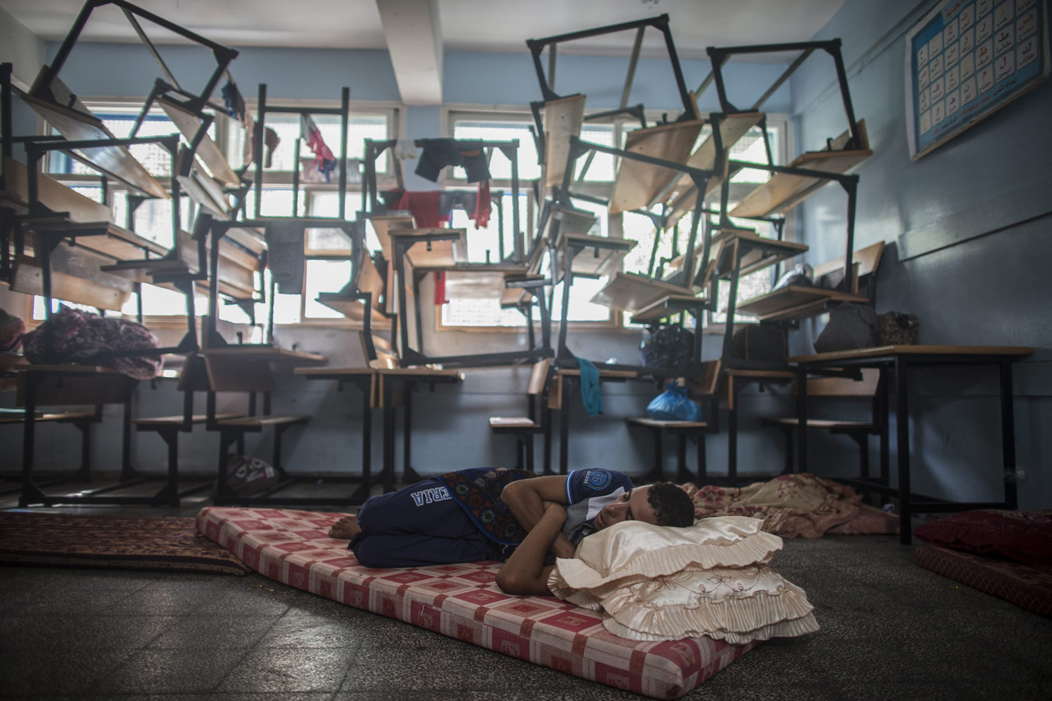 Jul. 13, 2014. A man who fled from Beit Lahiya, in the northern Gaza Strip, sleeps in a UN school which was transformed into a shelter in Gaza City.