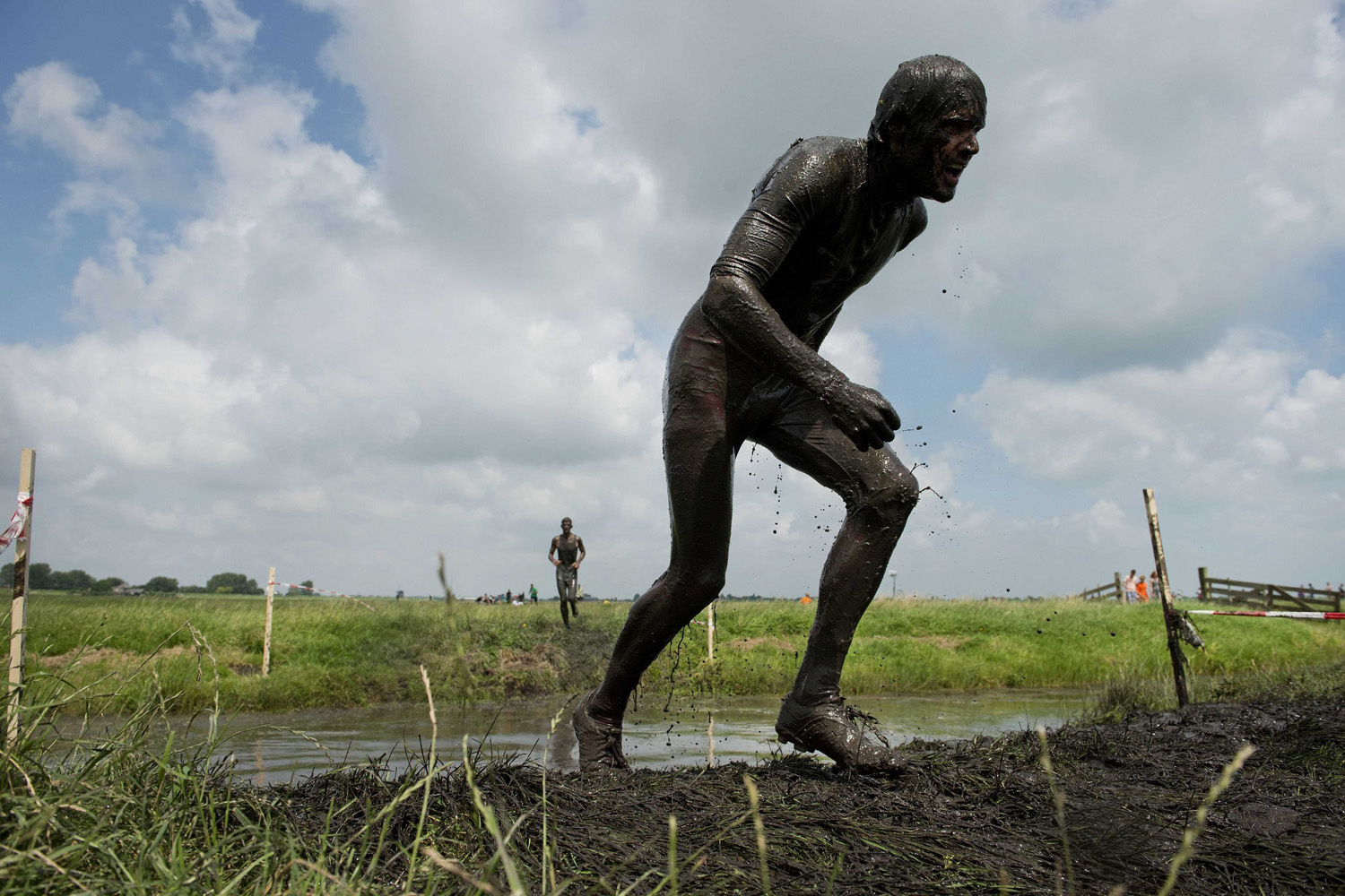 Jul. 13, 2014. A participant gets out of the water and continues on a muddy rack in the Dutch countryside during the so-called prutmarathon a race around a farmland track near Schermerhorn, the Netherlands.
