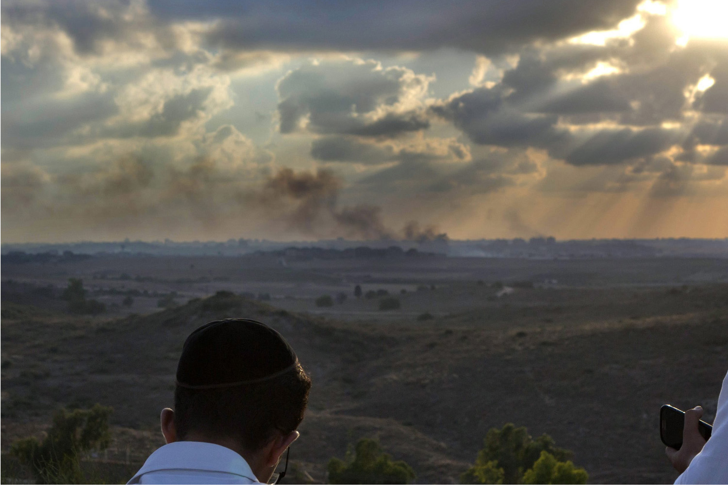 Jul. 17, 2014. Religious Israelis sit on a hill overlooking the Gaza Strip where black smoke rises from an Israeli air strike  as the sun sets.