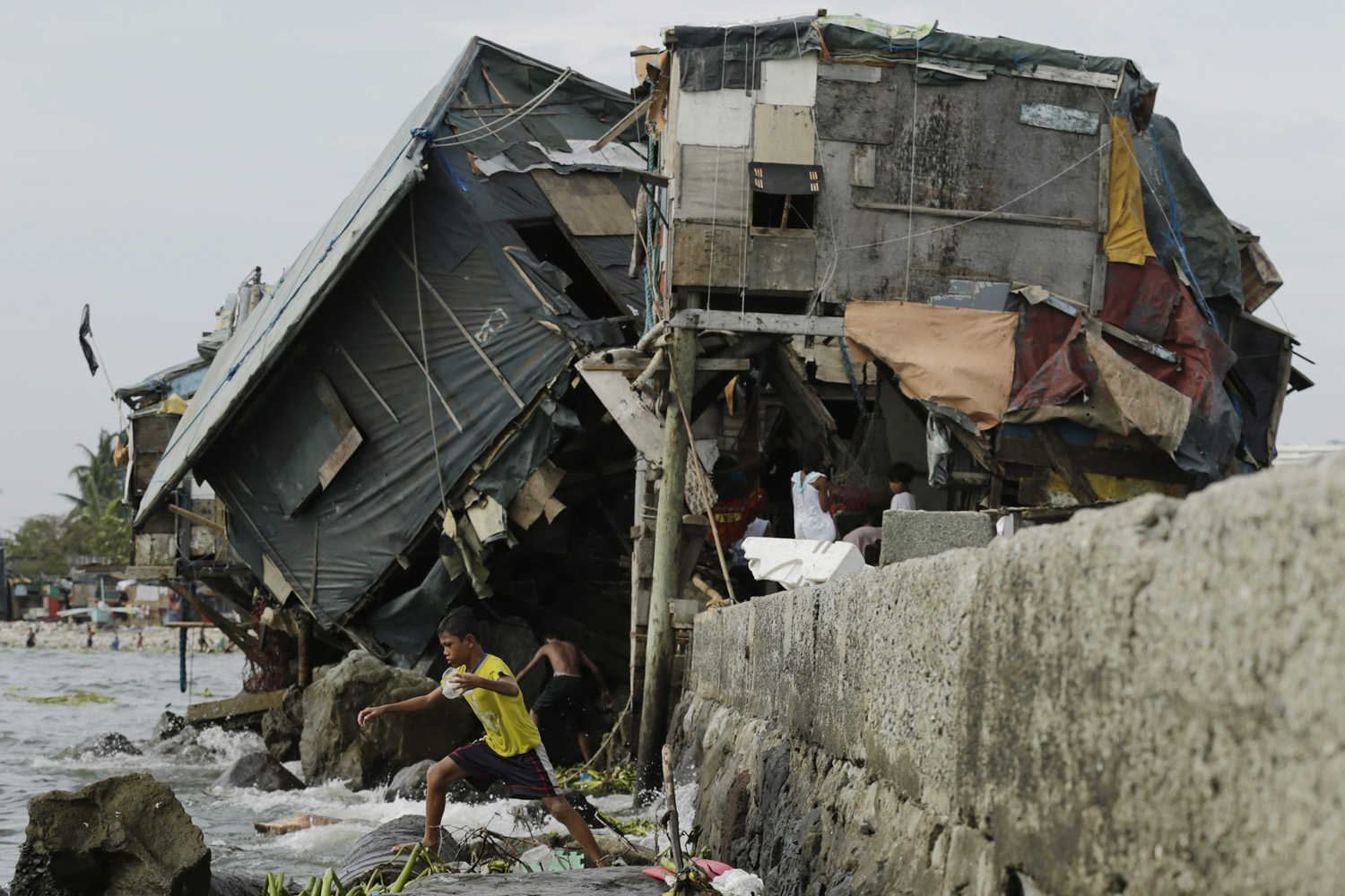 Jul. 18, 2014. A Filipino teen walks past a damaged house in Manila, Philippines, after strong winds and rain brought by Typhoon Rammasun  killed 60 people and left nearly two million in  the capital and eastern provinces  without power.