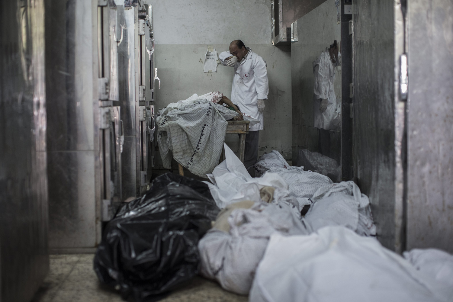 Jul. 20, 2014. A doctor cries while standing next to a table with the bodies of four dead children in the morgue of the Shifa hospital in Gaza City.