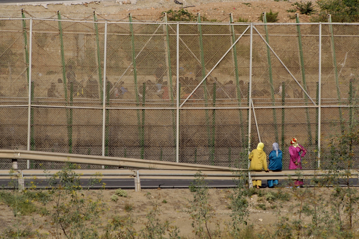 Jul. 23, 2014. Three women look at a group of Subsaharian immigrants who await on the other side of the fence bordering the Spanish city of Melilla with Morocco, in the Spanish enclave of Melilla, northern Africa