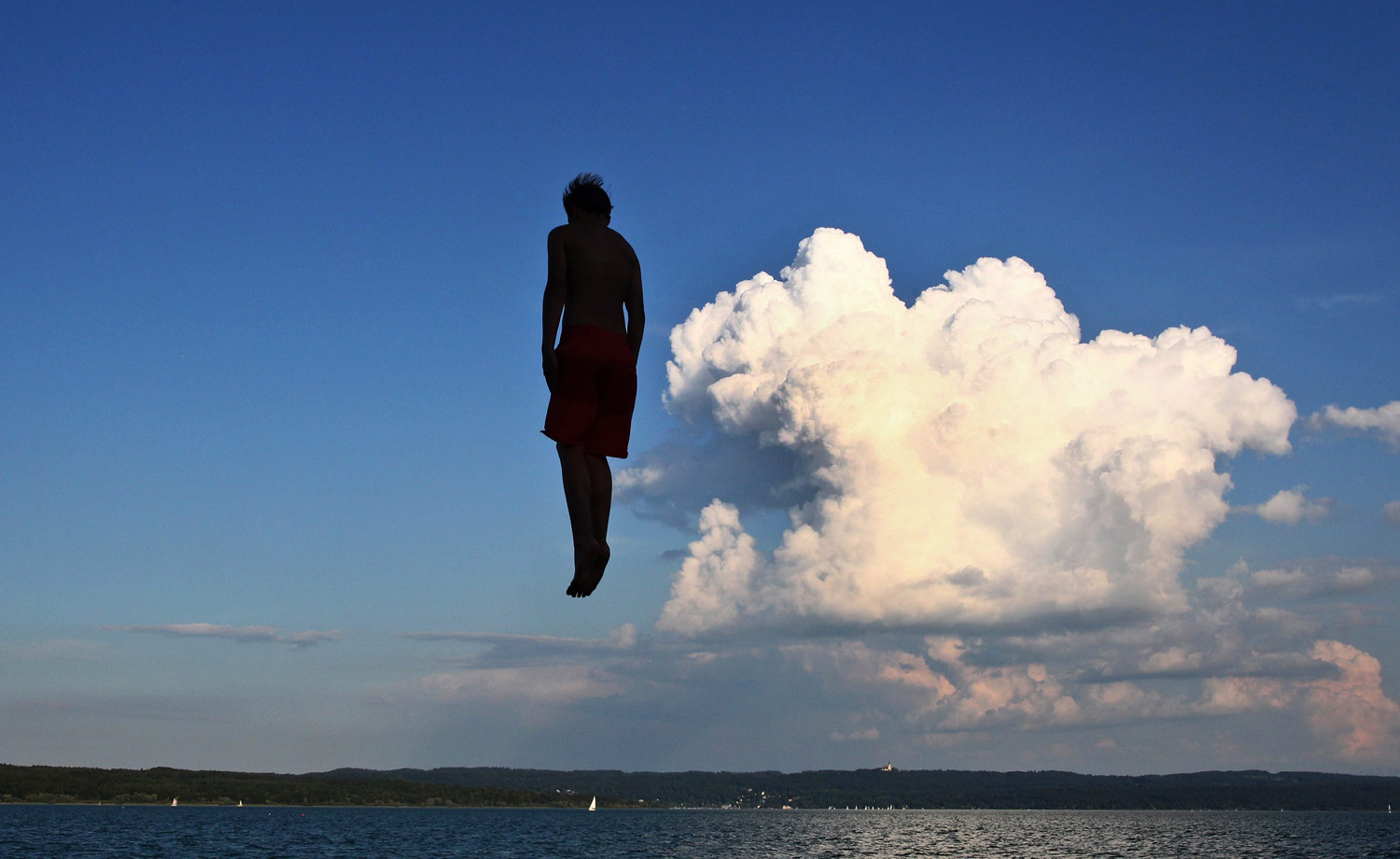 A young man jumps from a tower at a public bathing beach into the Lake Ammersee, in Utting, Bavaria state, Germany on July 23, 2014.
