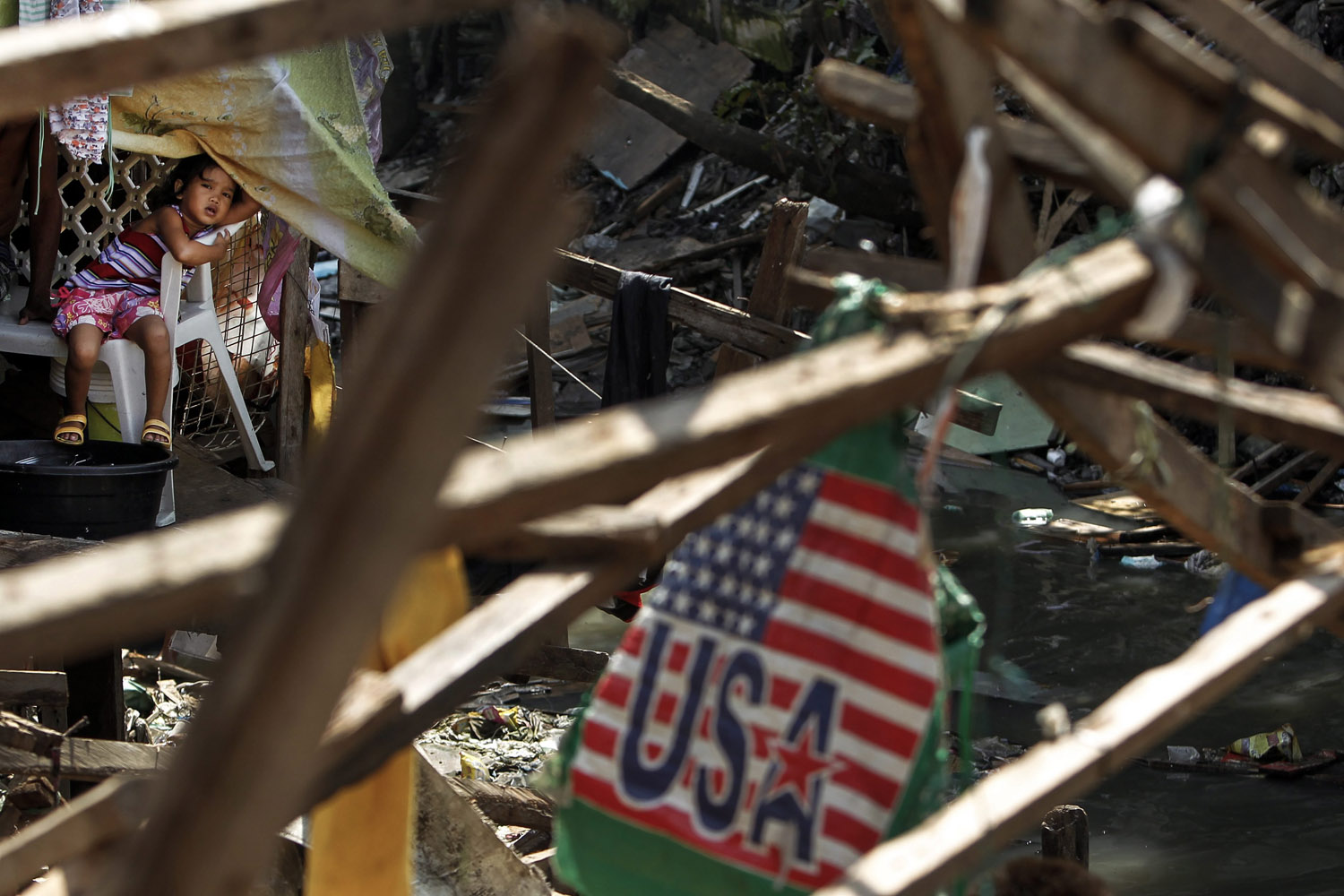 Jul. 23, 2014. A Filipino child looks from inside a shanty during a voluntary demolition at a slum area in Manila, Philippines.