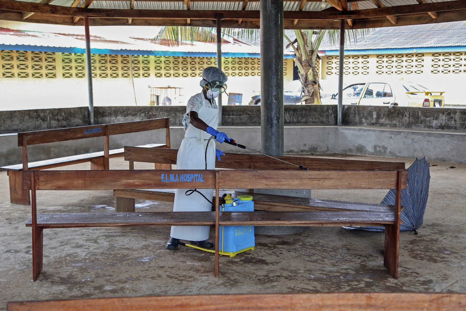 Jul. 28, 2014. A nurse from Liberia sprays preventives to disinfect the waiting area for visitors at the ELWA Hospital where US doctor Kent Bradley is being quarantined in the hospitals isolation unit having contracted the Ebola virus.
