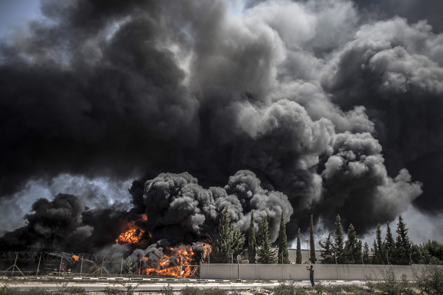 Jul. 29, 2014. A Palestinian man takes a picture of a fire raging in Gaza's main power plant following an overnight Israeli airstrike, south of Gaza City.