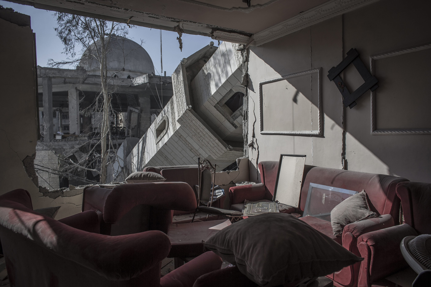 Jul. 31, 2014. The collapsed minaret of a mosque seen from the destroyed living room of a Palestinian family in a building across the street in Gaza City.