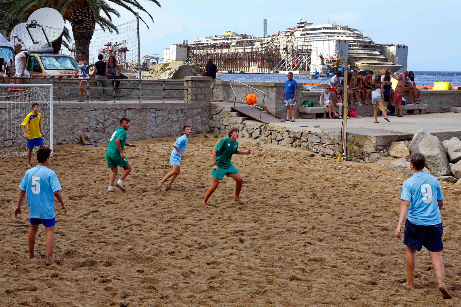 Youths play soccer at a beach as the Costa Concordia cruise liner is seen during its re-floating operation at Giglio harbor, Italy on July 22, 2014.