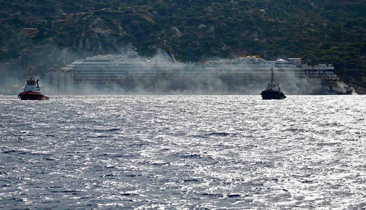 Black smoke comes out from the back of the Costa Concordia during its re-float operation at Giglio harbor, Italy on July 23, 2014.