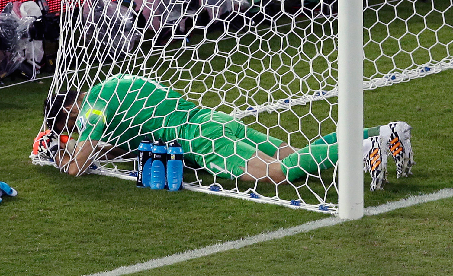 Greece's goalkeeper Orestis Karnezis sits in the net during the group C World Cup soccer match between Japan and Greece at the Arena das Dunas in Natal, Brazil on June 19, 2014.