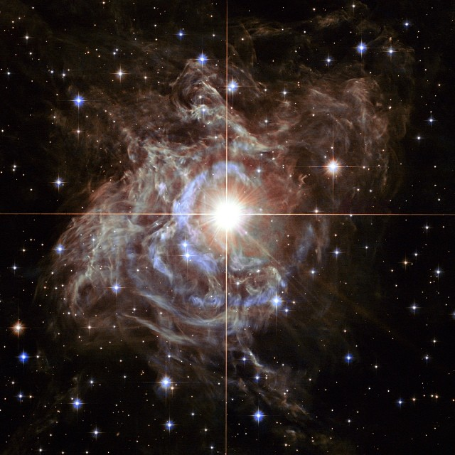 Dec. 18, 2013. This festive NASA Hubble Space Telescope image resembles a holiday wreath made of sparkling lights. The bright southern hemisphere star RS Puppis, at the center of the image, is swaddled in a gossamer cocoon of reflective dust illuminated by the glittering star. The super star is ten times more massive than our sun and 200 times larger.