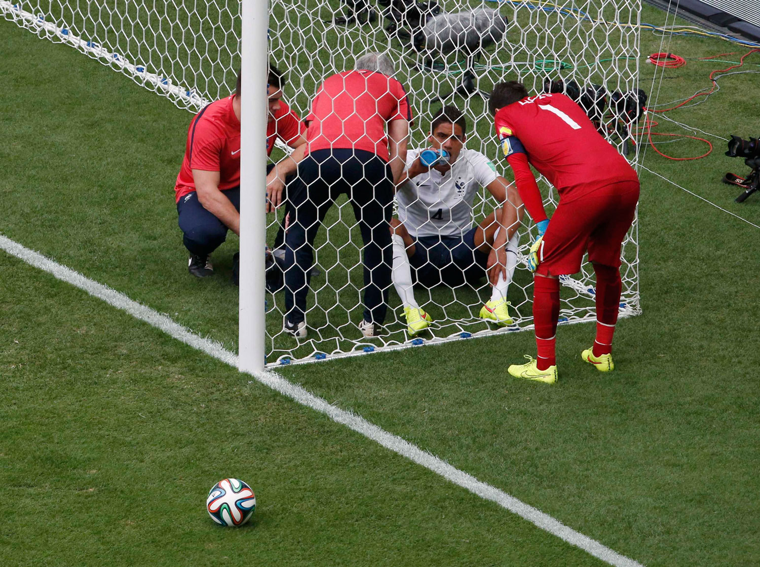 France's goalkeeper Hugo Lloris looks at teammate Raphael Varane who sits in the net after being hit in the face by a ball, during their game against Nigeria at the Brasilia National Stadium in Brasilia, Brazil on June 30, 2014.