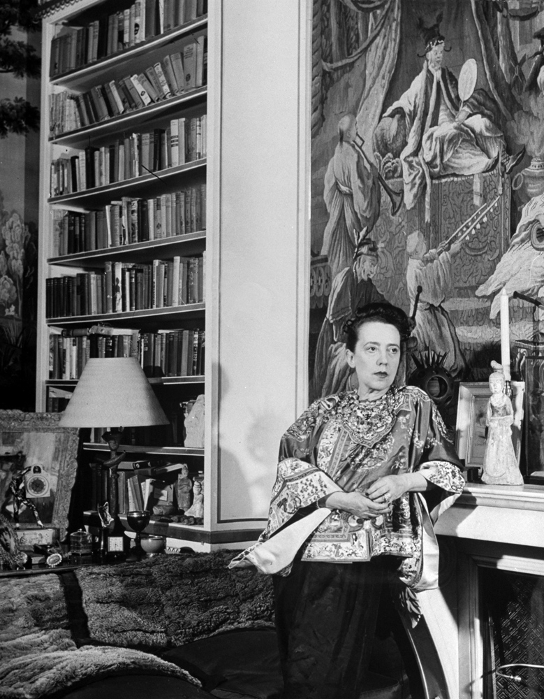 Fashion designer Elsa Schiaparelli in her study -- filled with treasures, paintings and books -- in Paris, 1947.