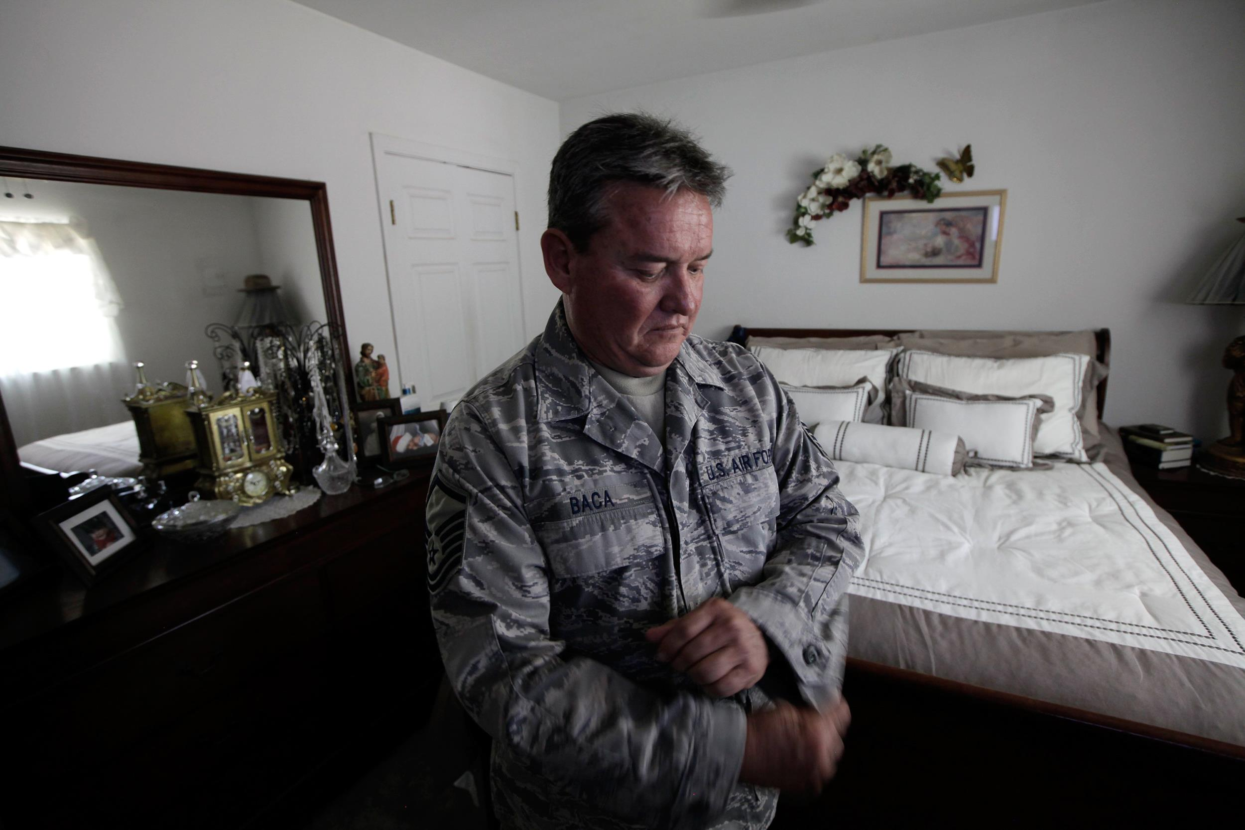 Master Sgt. Jessey Baca, who has constrictive bronchiolitis, adjusts his uniform at home on July 2, 2014