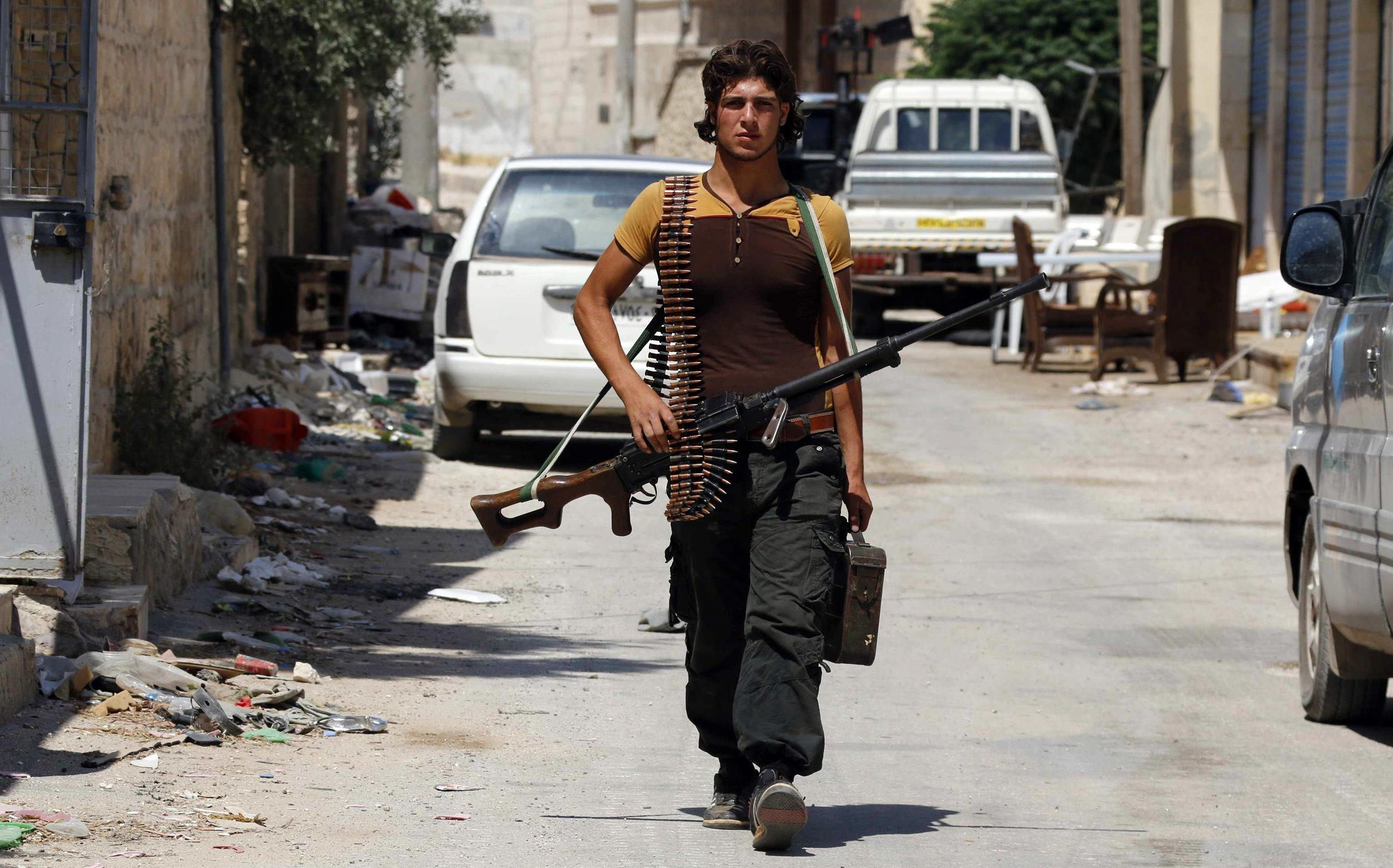 A rebel fighter walks with his weapon at the Handarat camp frontline, an area located beside Aleppo Central prison July 6.