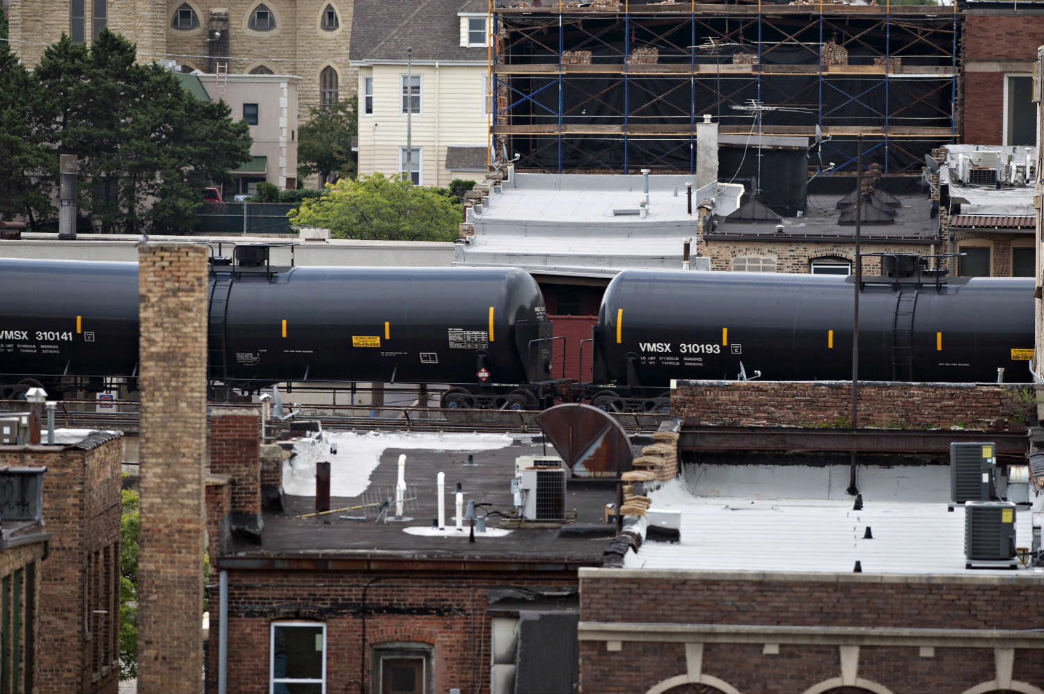 Oil-laden rail cars pass through densely populated towns like Aurora, Illinois