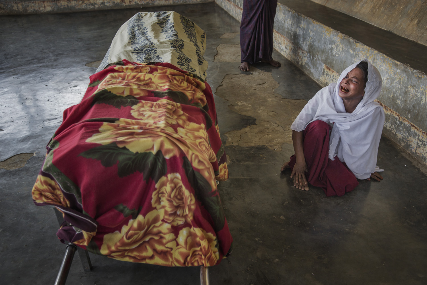 A mourner weeps as she sits by an internee's coffin. The Rohingya lack medical care since most NGOs are now barred from the camps.
