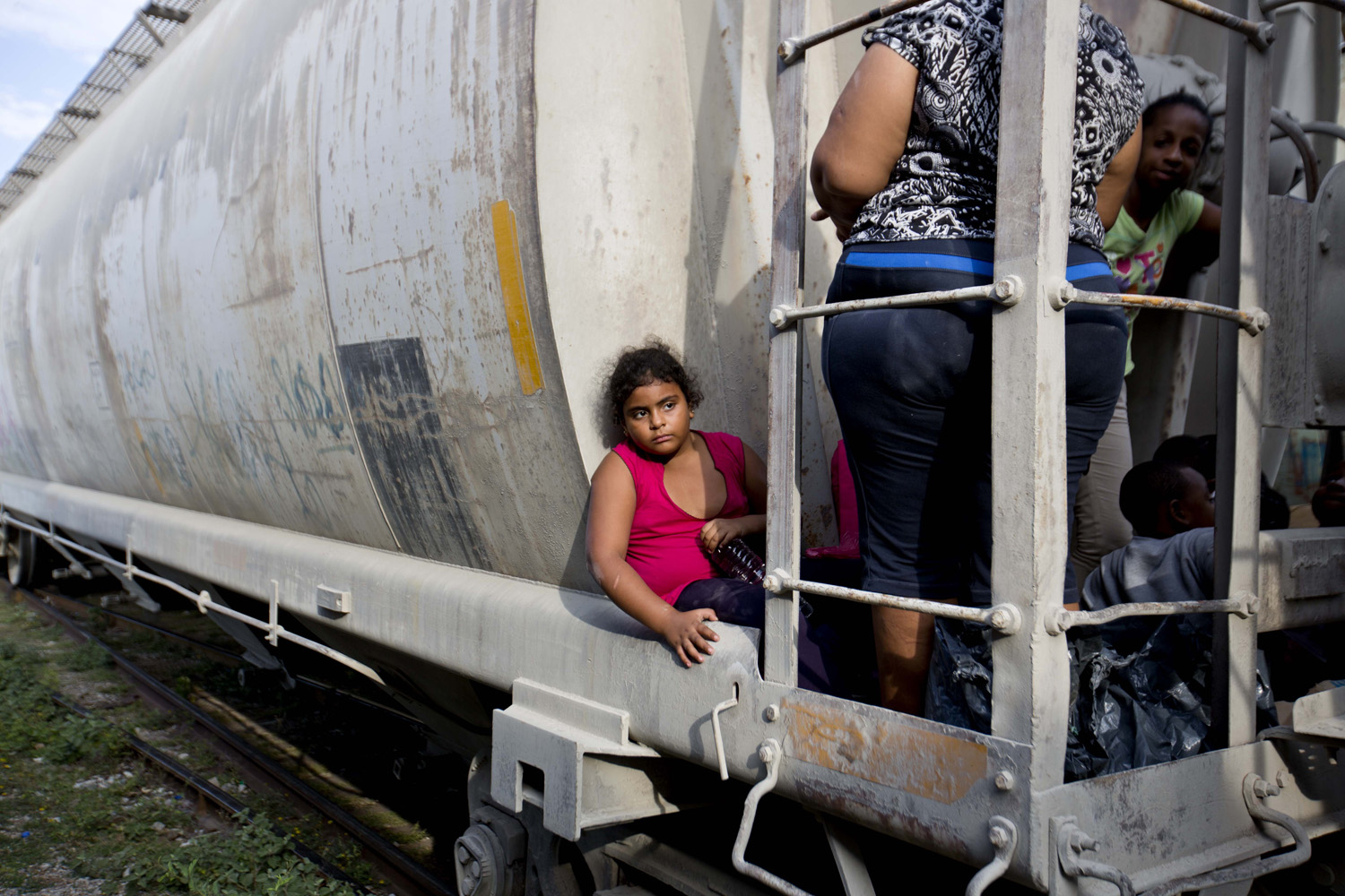 A young girl from Honduras waits for a northbound freight train to depart in Mexico as she makes her way to the U.S. border