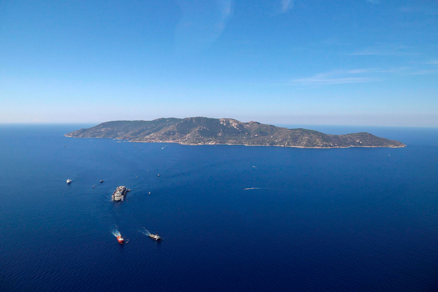 An aerial photo of the wrecked Italian cruise liner the Costa Concordia as it is towed on its final journey to the port of Genoa, Italy from Giglio Island, Italy 240 kilometers away on July 23, 2014.