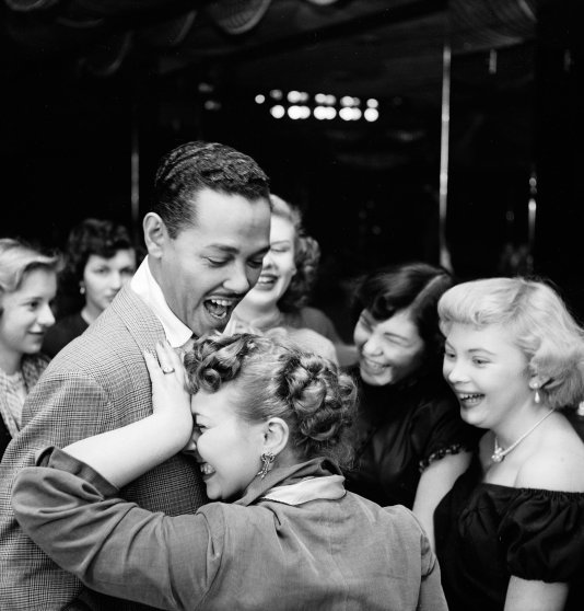 Singer and bandleader Billy Eckstine gets a hug from an adoring fan after a show at the late, great New York City jazz club, Bop City, 1949.