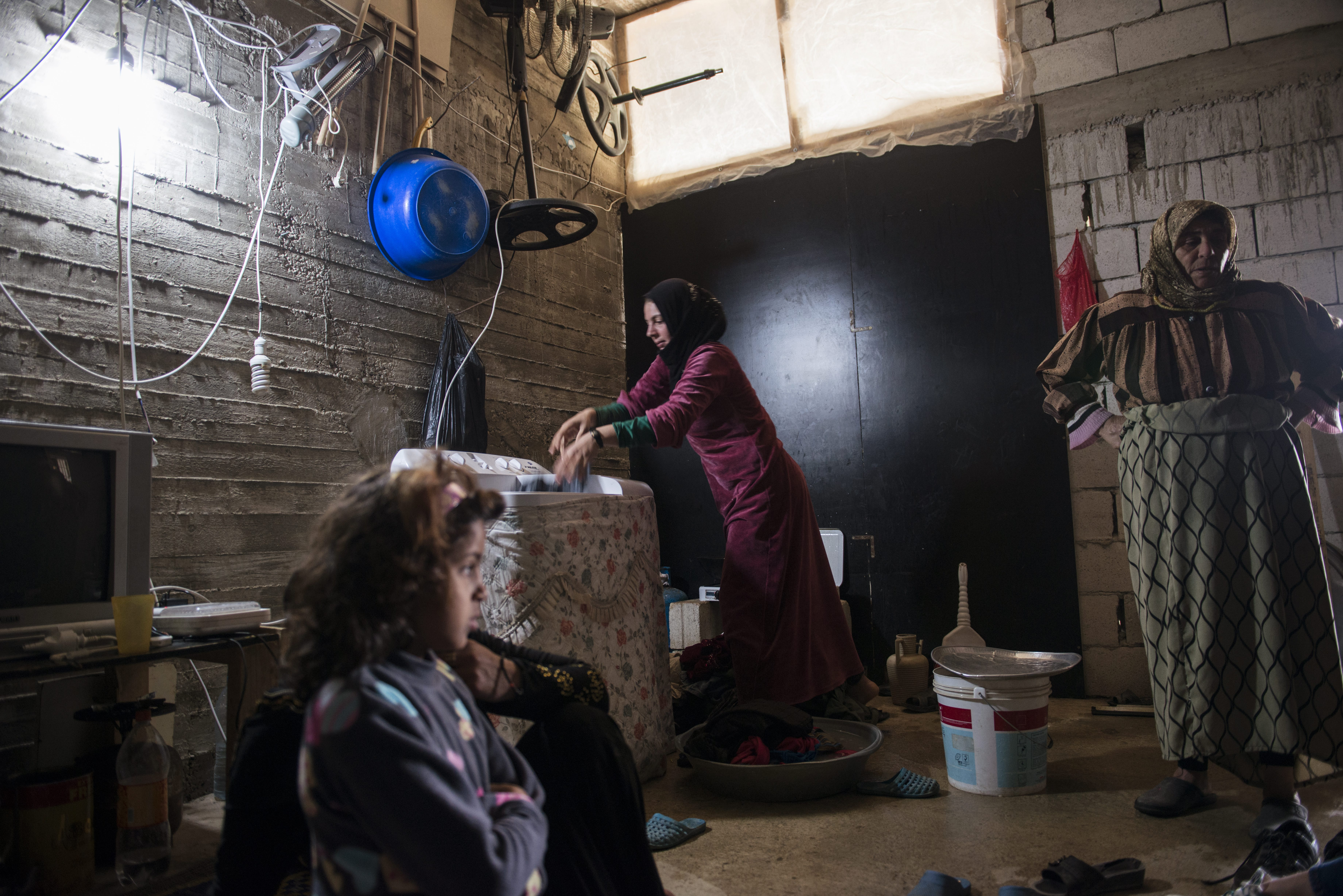 Sanaa, 26, washes clothes in a borrowed washing machine at a shelter in Saida, Lebanon, on March 4, 2014.