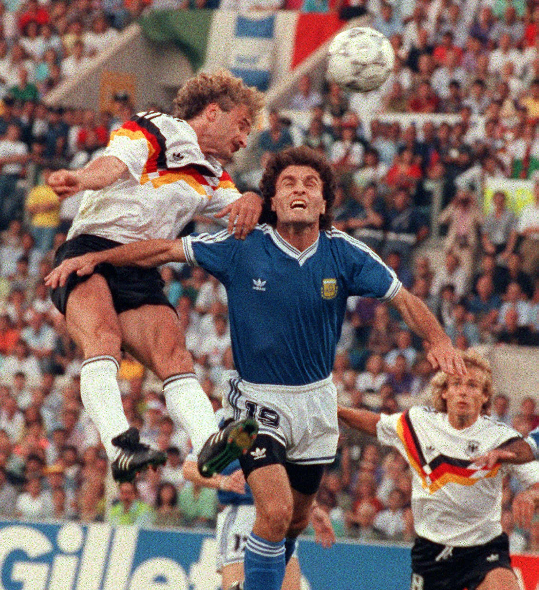 West German forward Rudi Voeller heads the ball over Argentinian defender Oscar Ruggeri as forward Juergen Klinsmann looks on during the 1990 World Cup final between West Germany and Argentina July 8, 1990 in Rome.