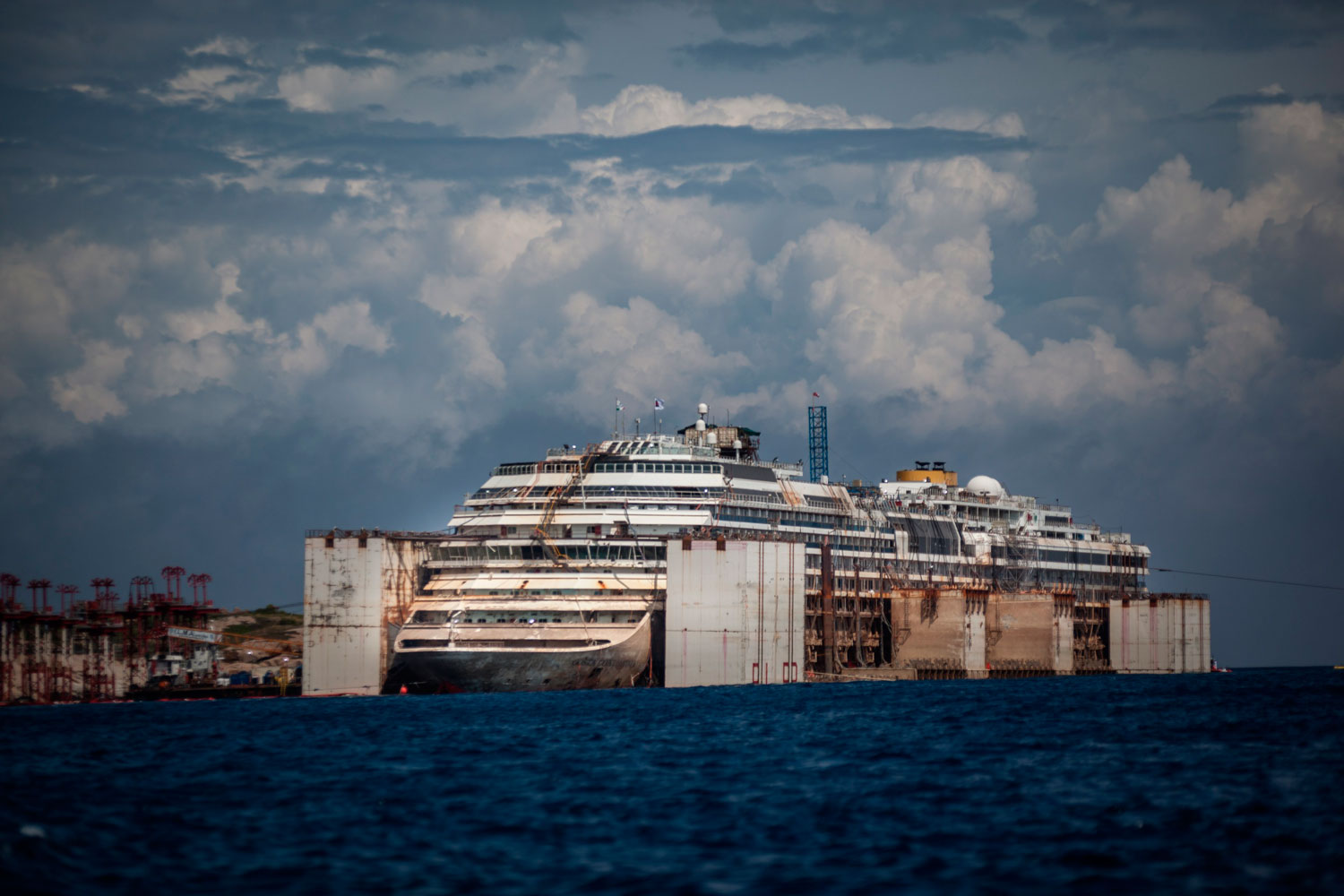 Costa Concordia re-float operation close to the end on July 21, 2014 in Giglio Porto, Italy. Air-filled steel boxes acted as pontoons, forcing the ship into an upright position.