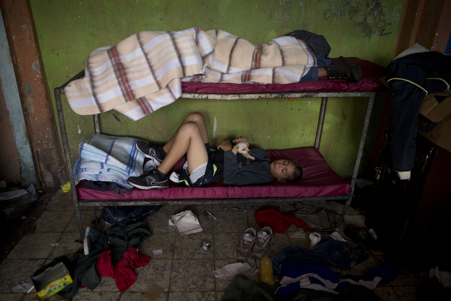 Jul. 17, 2014. A boy cuddles a puppy as he rests on a bunk inside The Great Family group home after a police raid, in Zamora, Mexico.