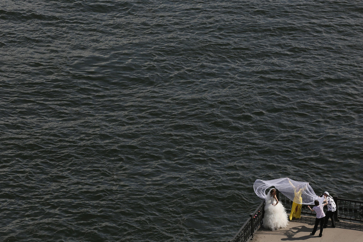 A bride poses for a photographer on an embankment at the Yenisei River in Russia's Siberian city of Krasnoyarsk, June 27, 2014.
