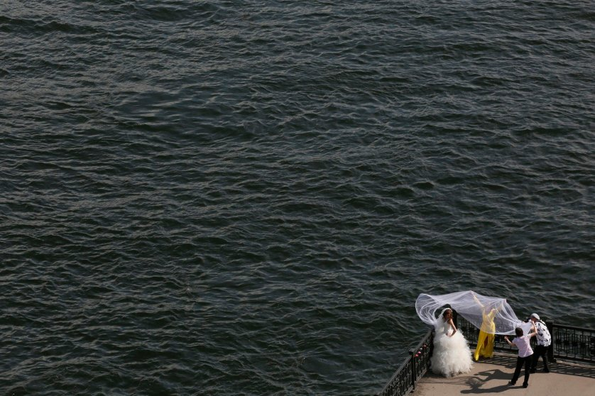 Bride poses for a photographer on an embankment at the Yenisei River in Russia's Siberian city of Krasnoyarsk