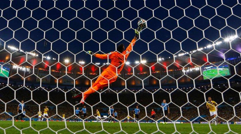 Colombia's James Rodriguez scores a goal against Uruguay's goalkeeper Fernando Muslera at the Maracana stadium in Rio de Janeiro on June 28, 2014.