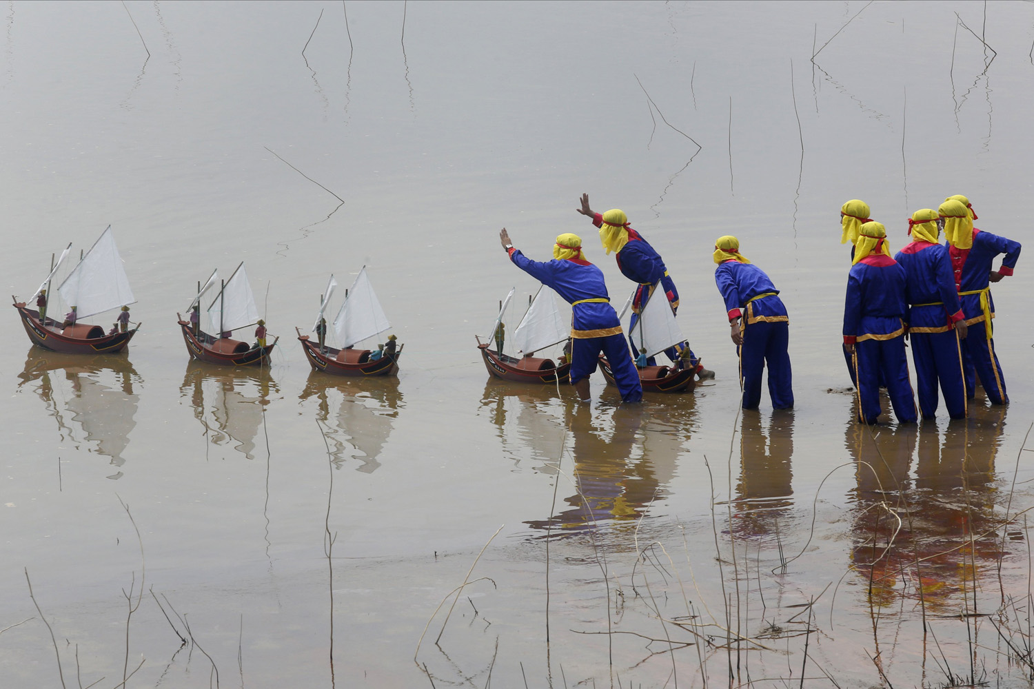 Jun. 29, 2014. Fishermen from Ly Son island release miniature fishing boat models with artificial soldiers into the water during a re-enactment of the Khao Le The Linh ceremony at a Vietnam Cultural village in Dong Mo, outside Hanoi.