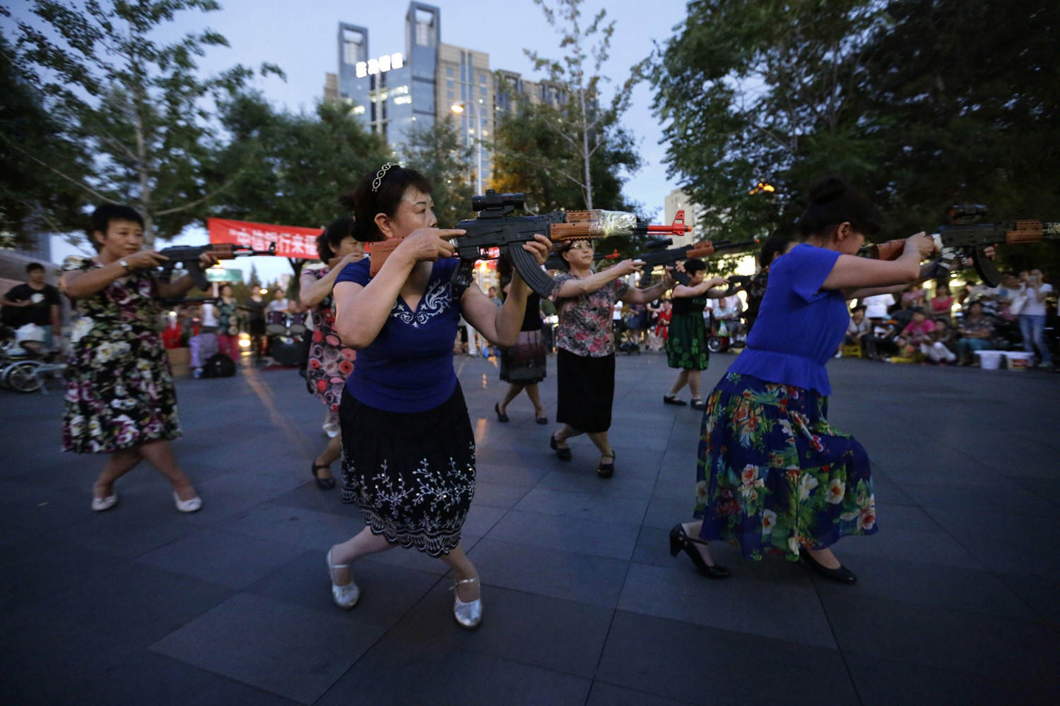 Jun. 27, 2014. Chinese women holding toy guns dance to a revolutionary song as part of their daily exercise at a square outside a shopping mall in Beijing.