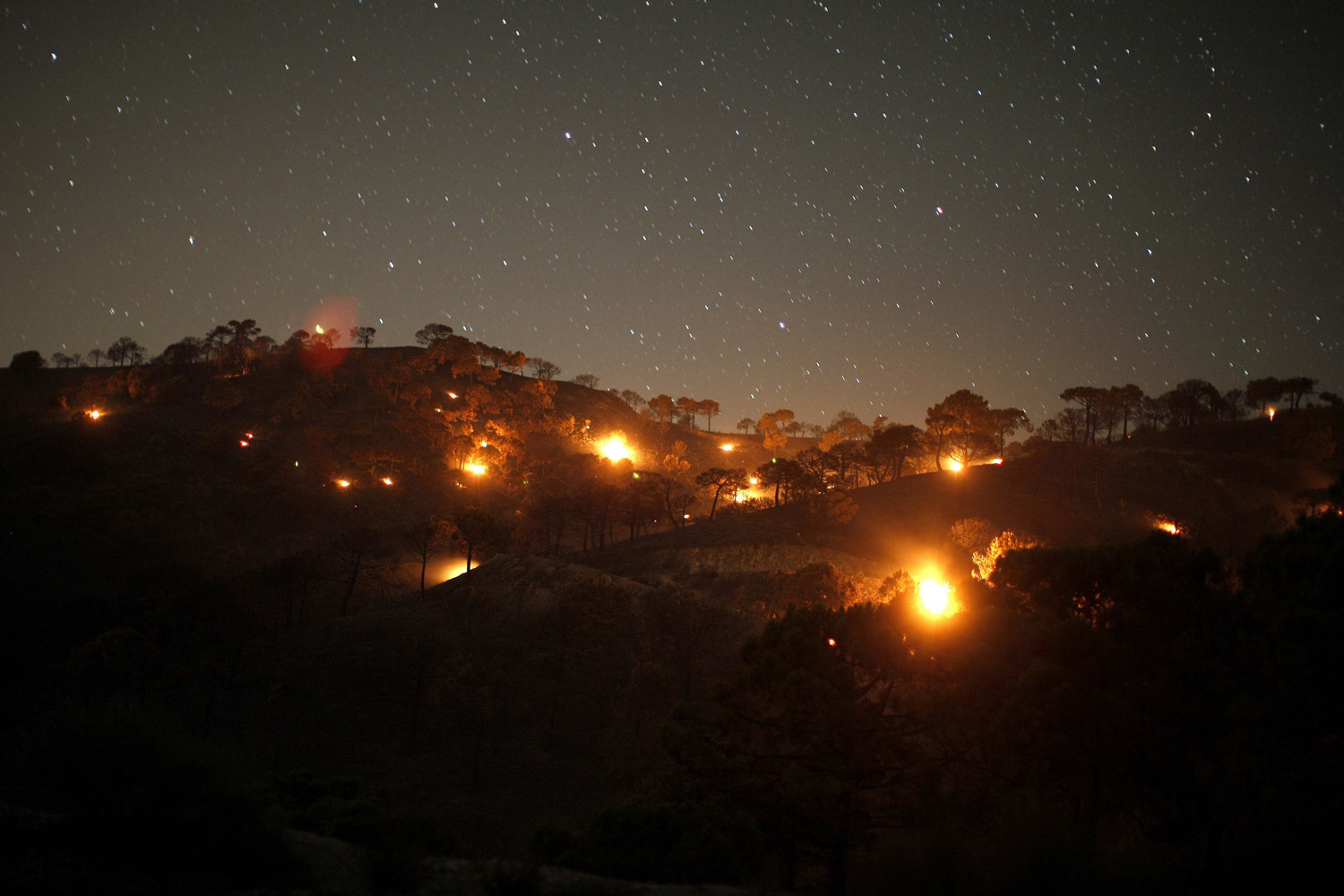 Jun. 30, 2014. Small forest fires are pictured between pine trees at night at Sierra de Tejeda nature park, on a burnt mountain from El Collado mountain pass, near the town of Competa, near Malaga, southern Spain.