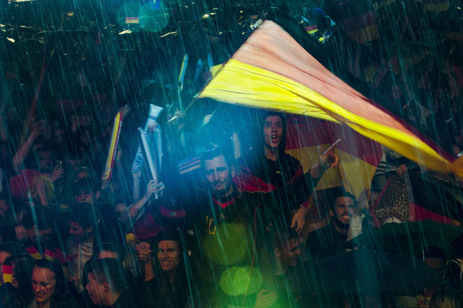 Jun. 30, 2014. People wave German flags as they watch Germany play against Algeria during their 2014 World Cup round of 16 game, during heavy rain at the Fanmeile public viewing arena in Berlin.