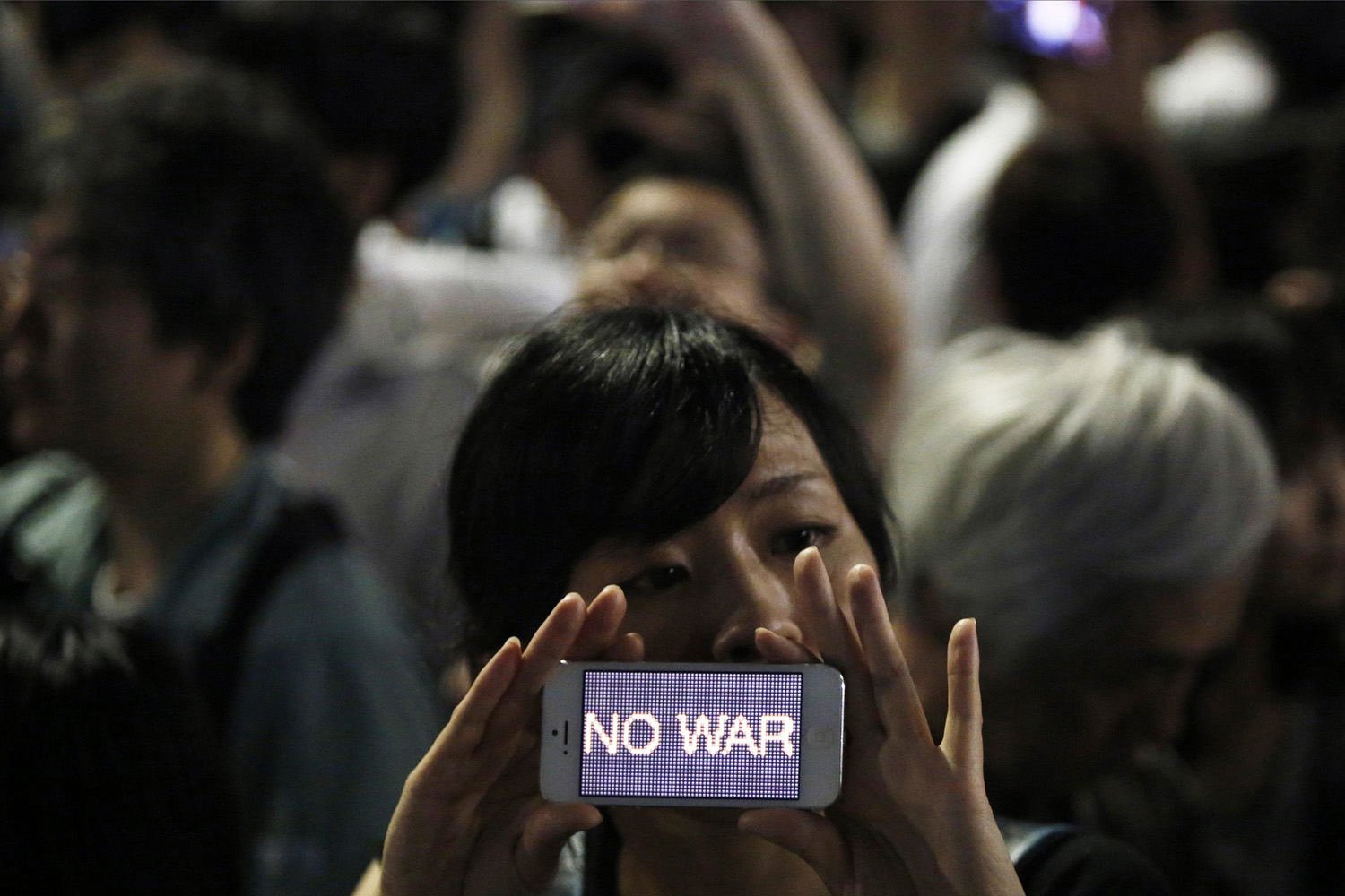 Jul. 1, 2014. A protester holds her smartphone displaying the phrase  NO WAR  at a rally against Japan's Prime Minister Shinzo Abe's push to expand Japan's military role in front of Abe's official residence in Tokyo.